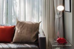 Brown und rotes Kissen auf braunem Sofa Lizenzfreie Stockbilder