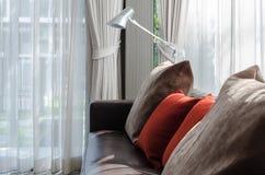 Brown und rotes Kissen auf Sofa mit Lampe im Wohnzimmer Lizenzfreies Stockfoto