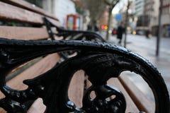 Brown und schwarze Holzbank neben Straße lizenzfreies stockfoto