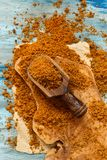 Brown unrefined cane sugar. On a blue wooden table top view Stock Photo