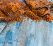 Brown unrefined cane sugar. On a blue wooden table close up Stock Images