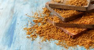 Brown unrefined cane sugar. On a blue wooden table close up Stock Photography