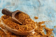 Brown unrefined cane sugar. With a spoon close up Royalty Free Stock Photos