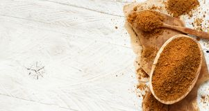 Brown unrefined cane sugar. On a wooden table close up Stock Image