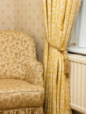 Brown vintage armchair near retro curtain Stock Image