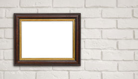 Brown vintage picture frame on white brick wall with copyspace