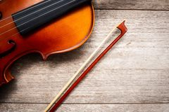 Brown violin with fiddle stick on wooden background. Art and mus royalty free stock photography