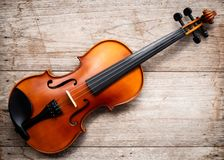 Brown violin on wooden background. Art and music background. Top stock images