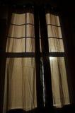 Brown-Vorhang mit dem Sonnenlicht, das durch Schattenbild des Fensters glänzt Stockfotografie