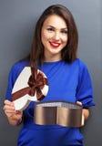 Brown włosiana uśmiechnięta dziewczyna z prezentem w serce formie Zdjęcia Royalty Free