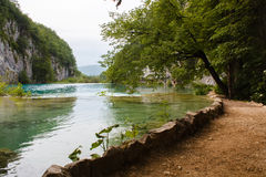Brown walkway surrounded with water mountains green grass and trees in National Park Plitvice Lakes in Croatia. Brown walkway surrounded with blue clear water Royalty Free Stock Image
