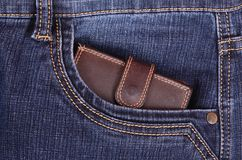 Brown wallet in the jeans pocket. Brown wallet in the blue jeans pocket stock photo