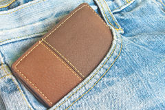 Brown wallet in jeans trousers back pocket Royalty Free Stock Images