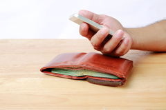 Brown wallet and Mobile phone in hand on wood background. stock images