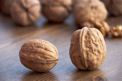 Brown walnuts. Whole brown walnuts on a wooden table Royalty Free Stock Photo