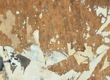 Brown, wei? und grau Die Fetzen von alten Plakaten auf einer Anschlagtafel stockfotografie