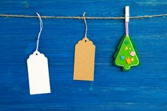 Brown and white blank paper price tags or labels set and Christmas felt decoration hanging on a rope on the blue background Royalty Free Stock Image