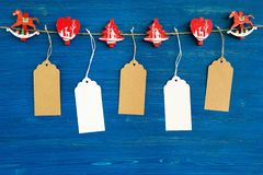 Brown and white blank paper price tags or labels set and Christmas wooden decoration hanging on a rope on the blue backgrou Stock Photo