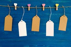 Blank paper price tags or labels set and wooden pins decorated on colored hearts hanging on a rope on the blue wooden background. Royalty Free Stock Photos