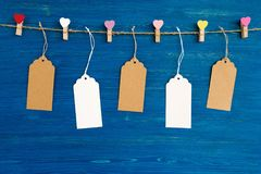 Blank paper price tags or labels set and wooden pins decorated on colored hearts hanging on a rope on the blue wooden background. Stock Photos
