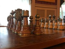 Chess game with window light. A brown and white chessboard on a wooden table Royalty Free Stock Images