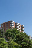 Brown and White Condo Tower in Green Trees Royalty Free Stock Image