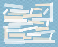 Brown and white different size adhesive, sticky, scotch tape, paper pieces on squared blue background. Royalty Free Stock Photos