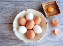 Brown and white eggs in white bowl and broken egg Stock Photos