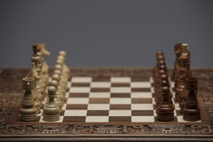 Brown and white figures on chess desk. Brown figures on chess desk standing. begin. over gray background Stock Photography