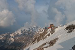 Brown and White House on Top of Snowy Mountain Under Grey Sky Stock Photography