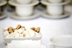 Brown and white refined sugar in square bowl with row of cups Stock Photos