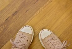 Brown and white shoes wooden floor. Brown and white sports woman`s shoes with laces, on brown wooden floor, photographed from the top down- A lot of copy space Royalty Free Stock Photo