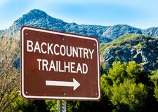 Brown and white sign pointing to Back country trail head in California. Brown and white metal sign pointing to Back Country Trail head in the Santa Monica Royalty Free Stock Photo