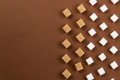 Brown and white sugar cubes on brown background Royalty Free Stock Photography