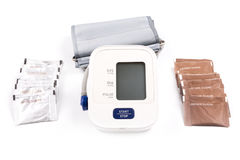 Brown and white sugar. Packs and blood pressure monitor  on a white background Stock Image