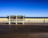Brown-and-white Wooden Bench Facing Body of Water Under Clear Blue Sky Stock Photos