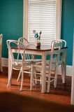 Brown and White Wooden Square Dining Table With Four White Chair Beside White Window Royalty Free Stock Photo