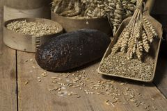 Brown whole grain loaves composition on rustic wood. Bread background. Brown whole grain loaves composition on rustic wood with wheat ears scattered around Stock Photography