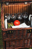 Brown wicker basket for picnic with tomato and glasses Royalty Free Stock Photo