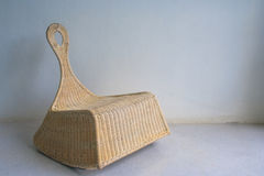 Brown wicker chair in vintage style on cement floor in white room. stock image