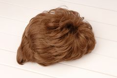 Brown wig is on white background,  curly-haired haircut. Wig Stock Photography