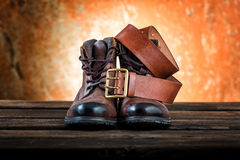 Brown winter boots and leather belt with buckle, wooden background Stock Images