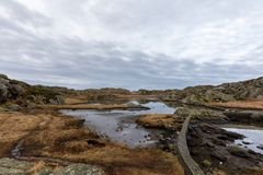 Brown winter landscape with beautiful sky. Pond by the trail, at the Rovaer archipelago, island in Haugesund, Norway. royalty free stock image