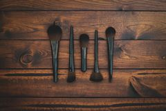 Brown wood background with assorted makeup brushes. stock images