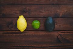 Brown wood background with Avocado, Lemon and Lime displayed. stock image
