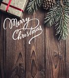 Brown wood background. Fir tree, decorative cone. Message space for Christmas and New Year. Gift for holidays. Xmas and Happy New. Year composition. Flat lay Stock Photo