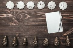 Brown wood background. With golden cones and sweet biscuits arranged diametrically opposed. Letter and space for a greeting message. Top View Stock Photography