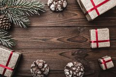 Brown wood background. greeting card. Fir tree, decorative cone. Message space for Christmas and New Year. Gifts for xmas. Sweet biscuits. Xmas and Happy New royalty free stock photography