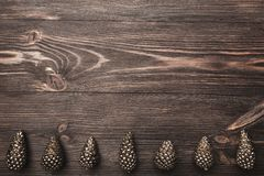 Brown wood background with pronounced texture. With golden cones at the bottom of the image. Space for a greeting message. Top View Stock Image