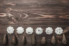 Brown wood background with pronounced texture. With golden cones at the bottom of the image and sweet biscuits. Space for a greeting message. Top View Stock Photography
